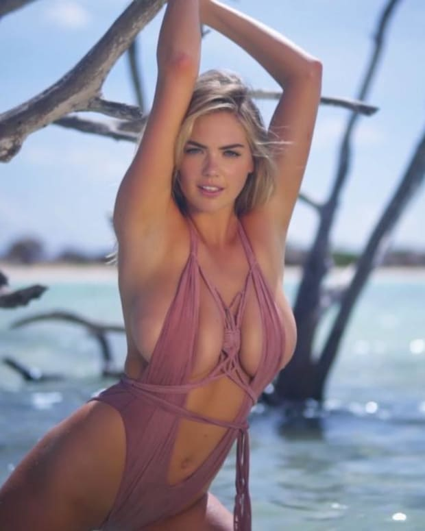 Kate Upton rolls around in the sand in Aruba
