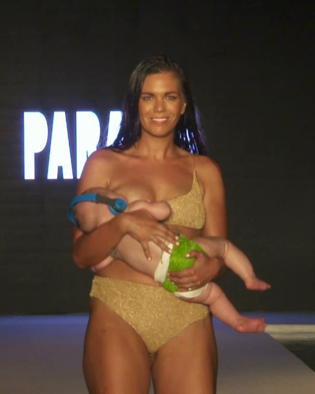 Mara Martin breastfeeds while walking the #SISwimSearch Runway