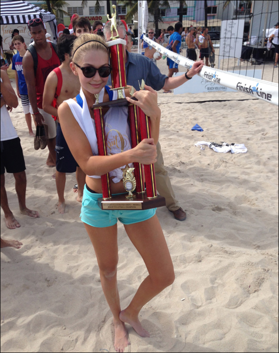 Gigi, who kept her junior Olympic volleyball experience under wraps during the models vs. celebrity chefs volleyball tournament, clings to her team's trophy. The unwieldy prize went home with Gigi to NYC, warranting its own seat on the charter flight.